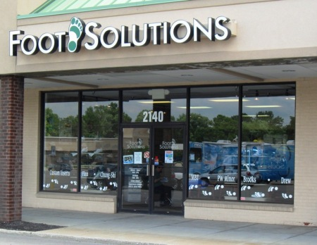 Can you find the Soles4Souls RV reflected in the Dayton Foot Solutions' store window?