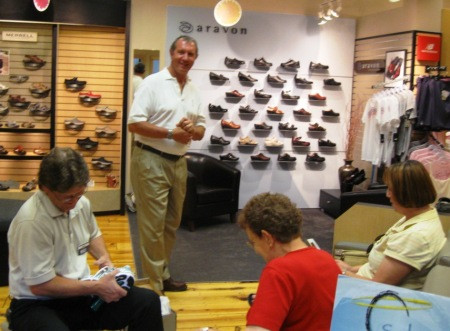 Manager Gary Larson serves as a customer as Allan explains Soles4Souls